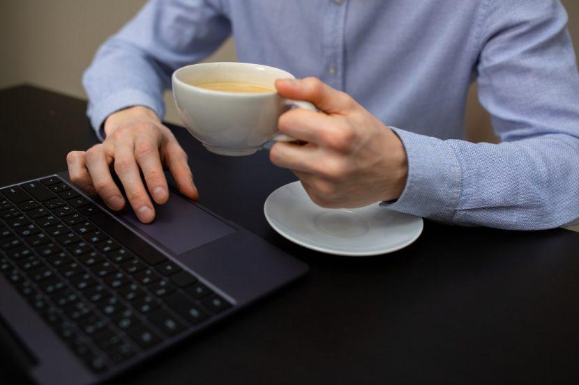 Man achter zijn laptop met remote monitoring en management software en een kop koffie